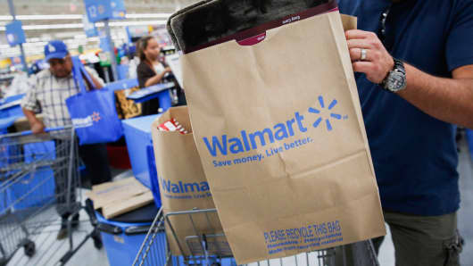 A customer puts a bag of purchases into a shopping cart at a Walmart Store in Los Angeles.
