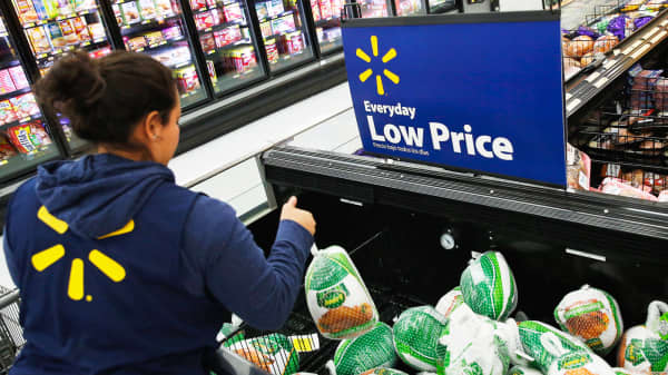 An employee arranges frozen turkeys displayed for sale at a Walmart Store in Los Angeles.
