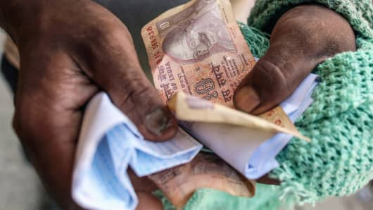 A worker holds Indian ten rupee banknotes in Mumbai, India.