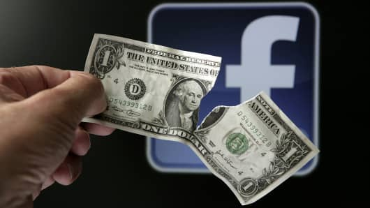 Torn dollar bill in front of Facebook logo