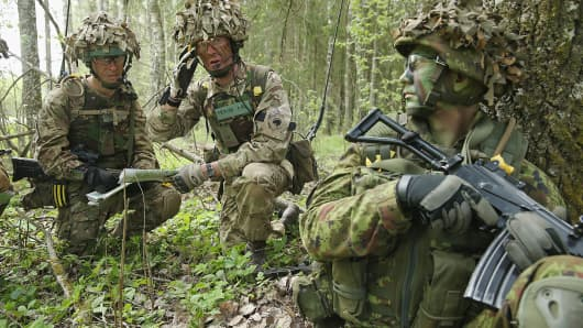 "Members of the British Duke of Lancaster's Regiment, left, plan their movements against the enemy while a member of the Estonian Scouts Battalion looks on in a forest during the NATO ""Spring Storm"" military exercises."