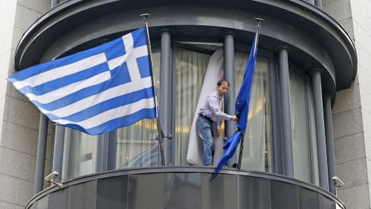 A man adjusts a European flag, next to a Greek flag outside the Greek embassy in Brussels February 19, 2015.