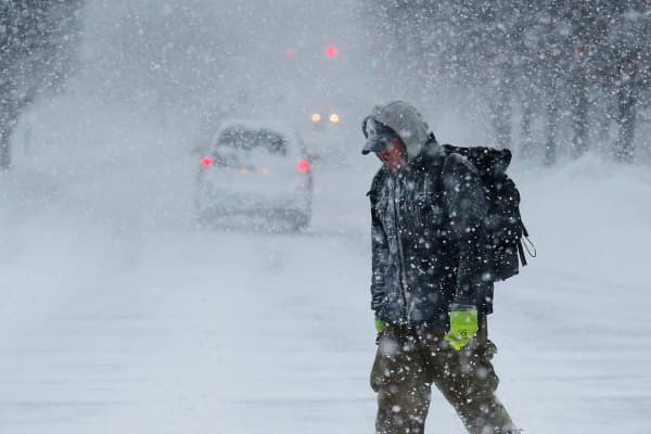 A pedestrian walks on the street through the snow during a winter blizzard in Cambridge, Massachusetts.