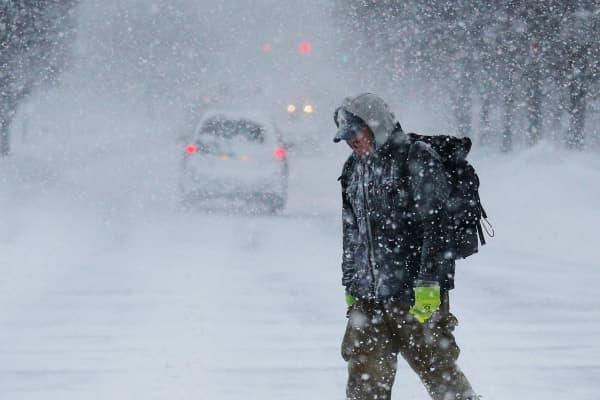 A pedestrian walks on the street through the snow during a winter blizzard in Cambridge, Massachusetts.