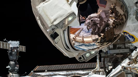 The mirrorlike visor of NASA astronaut Reid Wiseman reflects fellow astronaut Barry Wilmore during their Oct. 15, 2014, spacewalk outside the International Space Station.