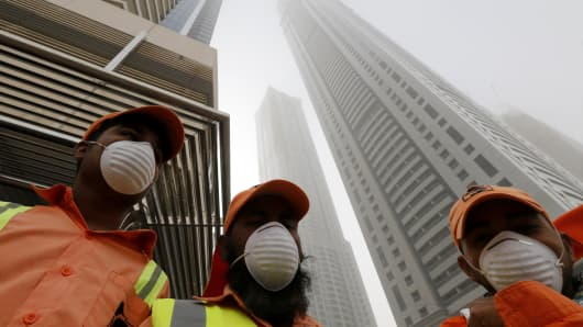 Municipal workers stand in front of the Torch skyscraper (C-Back) in the Gulf emirate of Dubai after a huge fire engulfed the residential tower early on February 21, 2015. The blaze has gutted the upper part of The Torch residential skyscraper.