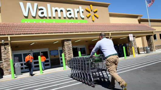A Wal-Mart employee pushes grocery carts at a store in Miami.