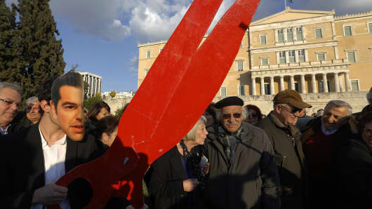A protester wearing a carnival mask depicting Greek Prime Minister Alexis Tsipras holds a pair of scissors as he takes part in an anti-austerity and pro-government demonstration in Athens February 15, 2015.