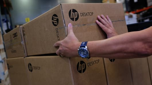 An employee selects a packaged HP desktop computer, produced by Hewlett-Packard Co., from a pallet in a warehouse.