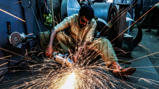 Sparks fly as an employee uses an angle grinder at an Ishwar Engineering factory in Mumbai, India.