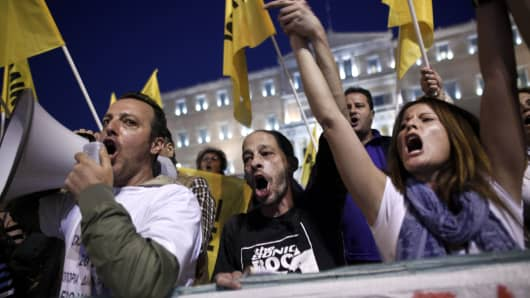 Protesters shout slogans during a rally in front of the Greek Parliament during a debate prior to a confidence vote in Athens in 2014.