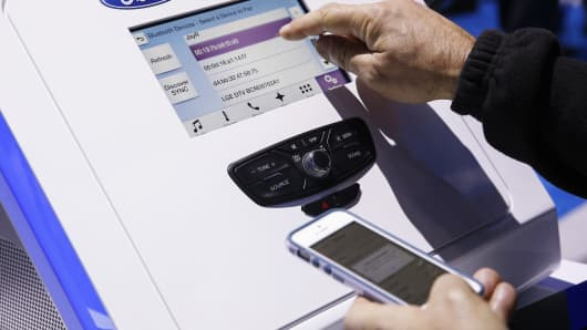 An attendee tries out an Apple Inc. iPhone via bluetooth with a Ford Motor Co. Sync AppLink interactive touchscreen display during the 2015 Consumer Electronics Show (CES) in Las Vegas, Nevada.