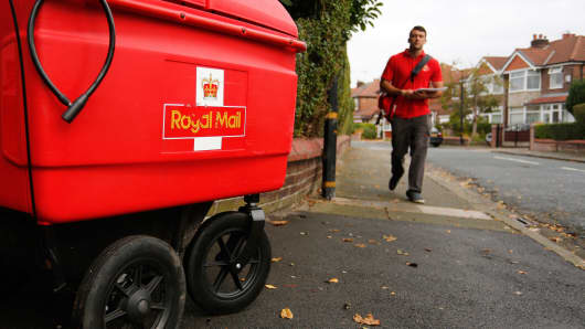 A Royal Mail Group postal worker on his delivery round in Manchester, U.K.