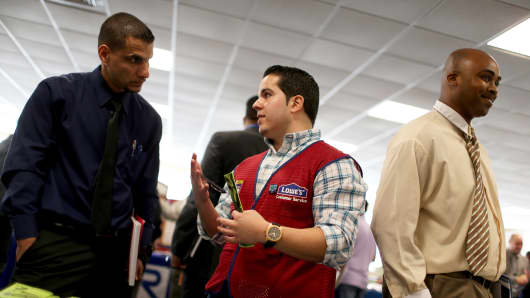 A U.S. military veteran listens as a manager with Lowes explains the jobs available in Miami.