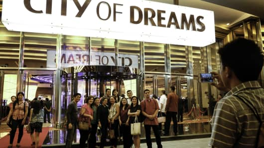 Visitors pose for a photograph below signage for the City of Dreams Manila casino resort