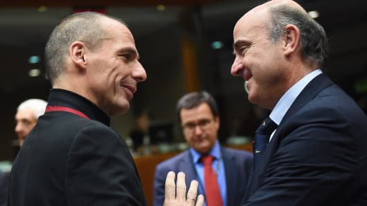 Greece's Finance Minister Yanis Varoufakis (L) speaks with Spanish Finance Minister Luis de Guindos Jurado as they arrive to take part in an European economic and financial affairs (ECOFIN) meeting at the European Council in Brussels, on February 17, 2015.