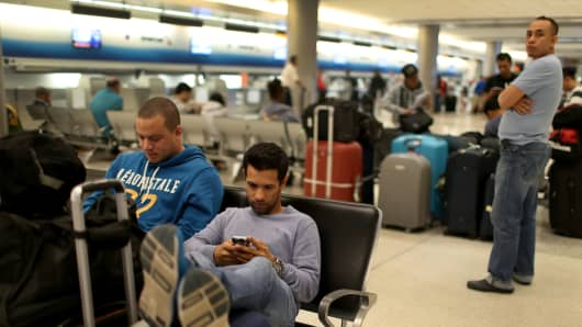Passengers sit after their flight to New York was cancelled at Miami International Airport on January 26, 2015 in Miami, Florida. Northeast coast airports are canceling thousands of flights as a major winter storm hits the North East U.S.