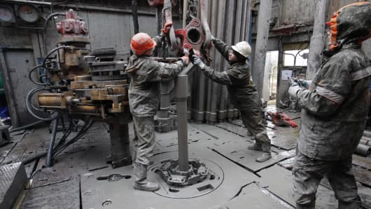 Contract workers fit drill pipe sections on the drilling floor of an oil rig in the Salym oilfields, operated by Salym Petroleum Development NV, near Surgut, Russia.