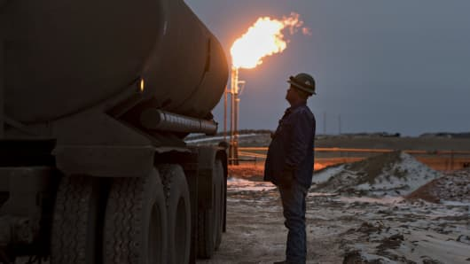 A gas flare burns an oil worker monitors a water tank while loading saltwater from an oil well storage tank near Sidney, Montana.