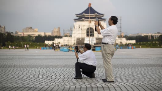 Chinese tourists take photographs at the Chiang Kai Shek Memorial Hall plaza in Taipei, Taiwan.