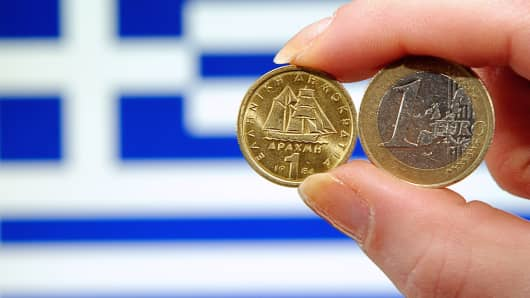 A one-euro coin and a one-drachma coin in front of a Greek national flag