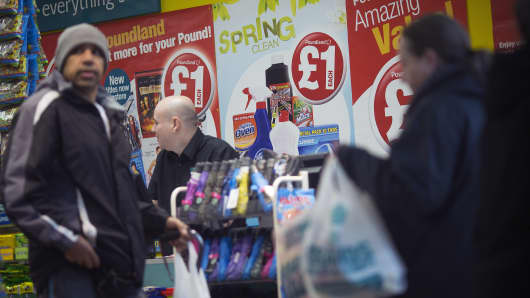 Customers wait at a check-out counter inside a Poundland discount store in London.
