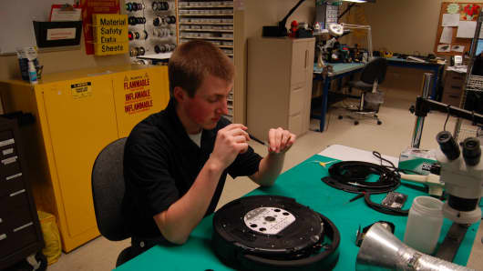 iRobot intern, Eric Peterson, working on a  Roomba robot.