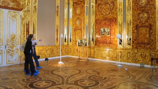 Visitors look at exhibits in the Amber Room in Catherine's Palace, near St. Petersburg, in Russia.