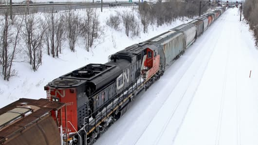 A Canadian National Railway train travels eastward on a track.