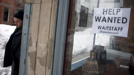 Pedestrians pass by a 'help wanted' sign in a restaurant in the Back Bay neighborhood on February 5, 2015 in Boston, Massachusetts.