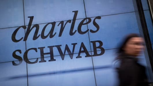 A pedestrian walks past a Charles Schwab office in New York.