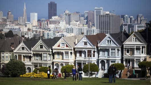 "The ""Painted Ladies,"" a row of historical Victorian homes, are shown with the San Francisco skyline in the background."