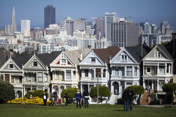 """The """"Painted Ladies,"""" a row of historical Victorian homes, are shown with the San Francisco skyline in the background."""