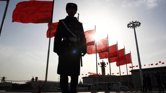 A paramilitary police officer stands guard in front of red flags at Tiananmen Square in Beijing, China, on Monday, March 2, 2015.