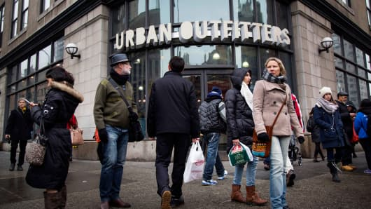 Pedestrians walk past an Urban Outfitters store in New York.