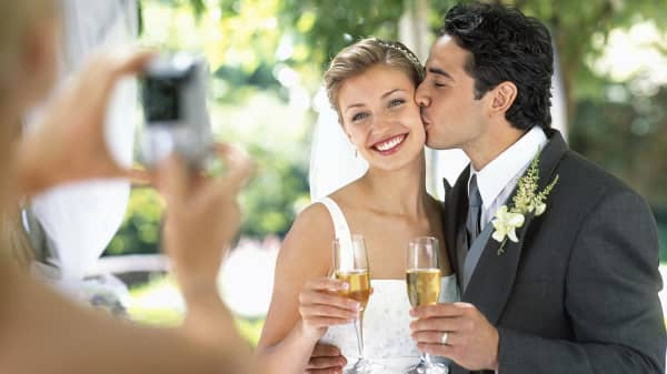 Woman photographing bride and groom