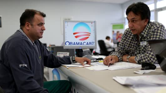 A customer sits with an insurance advisor with UniVista Insurance company, as he signs up for the Affordable Care Act, also known as Obamacare, before the February 15th deadline on February 5, 2015 in Miami, Florida.