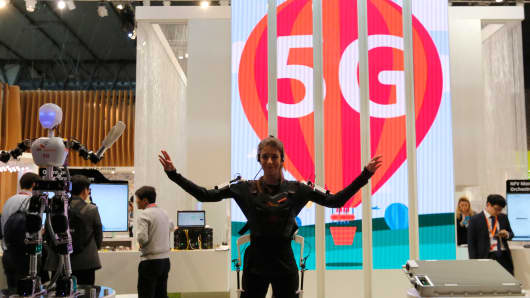 An SK telecom exhibitor directs the robot's movements using 5G at the Mobile World Congress in Barcelona, March 5, 2015.