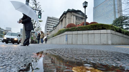A pedestrian walks in front of the Bank of Japan headquarters