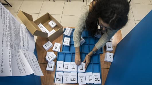 An Israeli polling station worker arranges ballots during Israel's general elections on March 17, 2015.