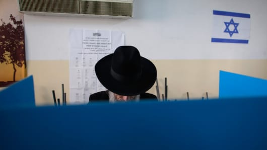 A ultra-Orthodox Jewish man stands behind a voting booth at a polling station in Jerusalem March 17, 2015.