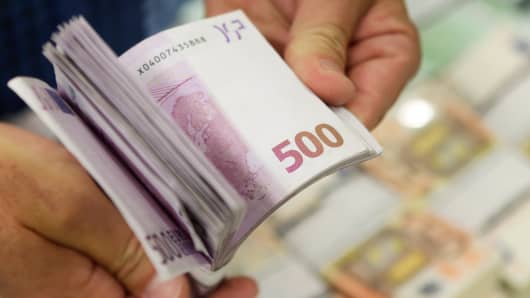 An image of Euro banknotes being counted.