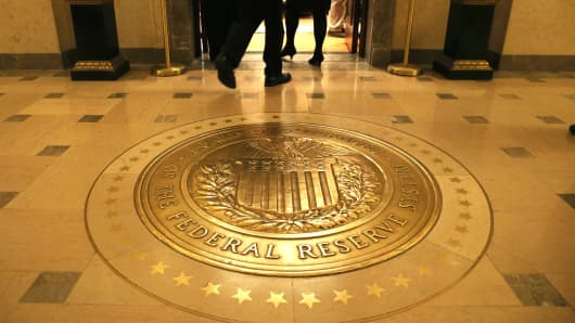 People walk into a meeting of the Board of Governors at the Federal Reserve in Washington DC.