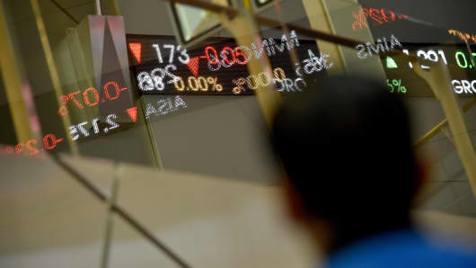 An Indonesian man looks at a running display showing share prices at the stocks exchange building in Jakarta.