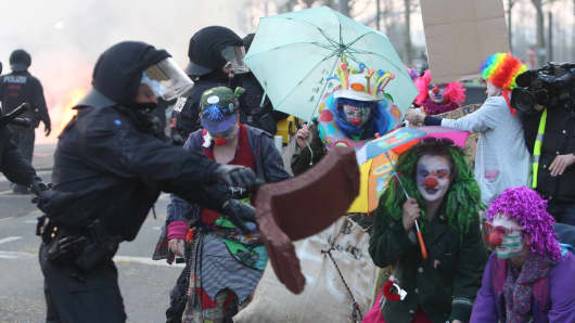 Riot police clash with protesters dressed as clowns on the opening day of the European Central Bank (ECB) in Frankfurt am Main, western Germany, on March 18, 2015.