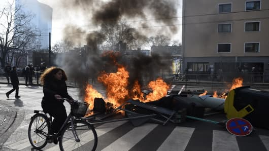 A woman cycles by a burning barricade as the ECB building is seen on the left, on the opening day of the European Central Bank (ECB) in Frankfurt am Main, western Germany, on March 18, 2015.