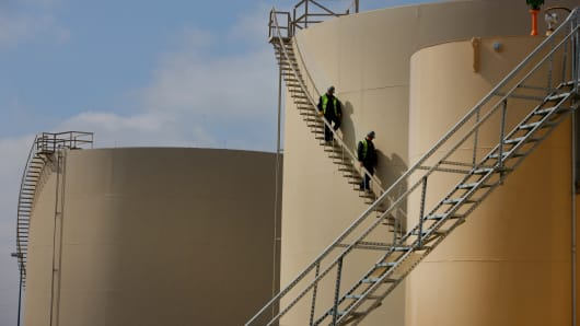 Workers walk down the stairs of an oil storage tank at the Musket Corp. Windsor Crude Terminal in Windsor, Colorado.