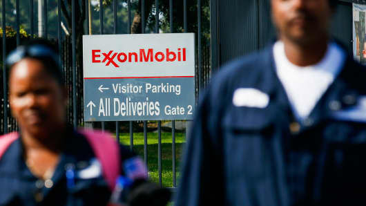 Exxon Mobil workers walk near an entrance to a company location.