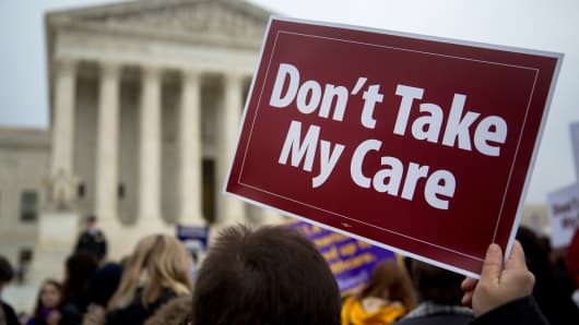 A demonstrator holds a sign in support Obamacare in front of the Supreme Court in Washington.