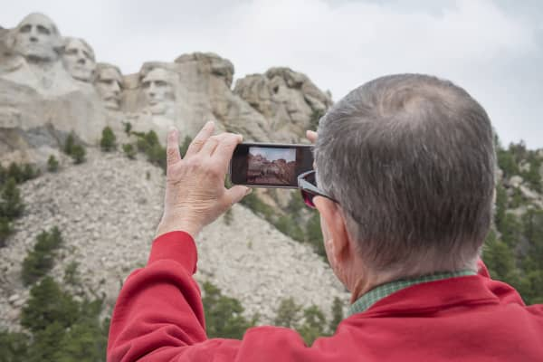 Senior man photographing Mount Rushmore